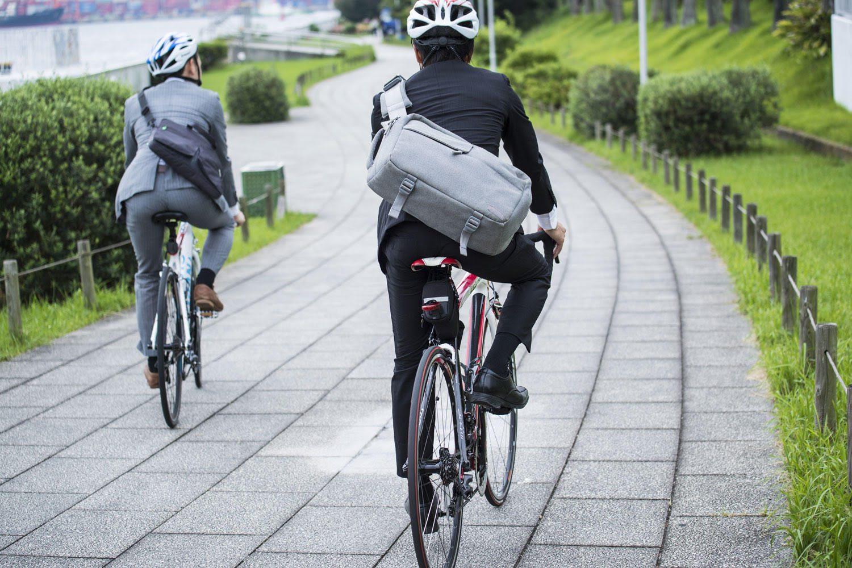 2 Radfahrer am Weg in die Arbeit mit Anzug